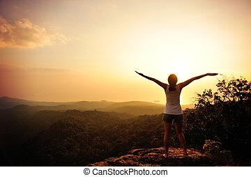 cheering woman open arms at sunset