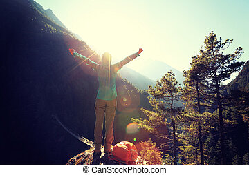 cheering young woman hiker open arms to the sunrise at the himalaya mountains
