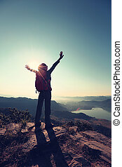cheering young woman hiker open arms to the sunrise