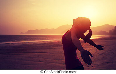 Cheering young woman with open arms on sunrise beach