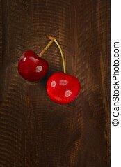 Cherry red fruits over dark wooden