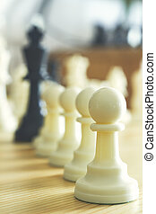 chess pawns lined up in a row , Leader success concept