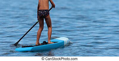 Child boy paddling on stand up paddleboard