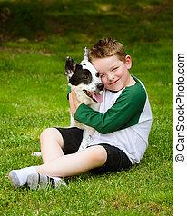 Child lovingly embraces his pet dog