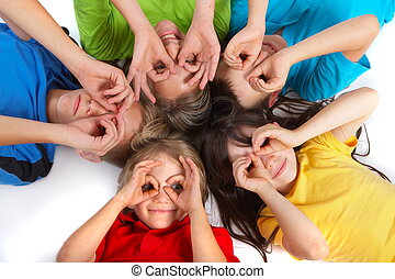 Five children laying in a circle with their heads touching, playfully holding their hands in circles like eyeglasses over their eyes. Isolated on white background.