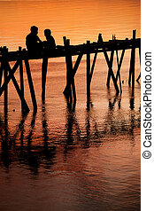 Children on bridge sunset silhouette