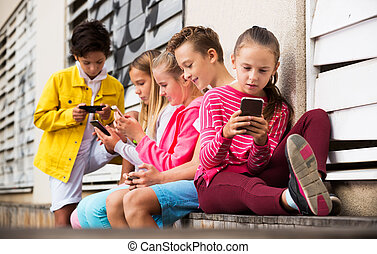 Children playing on smartphone outdoors