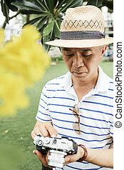 Chinese man checking digital camera