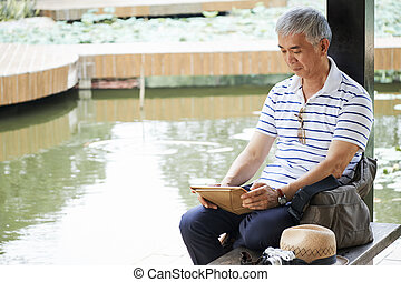 Chinese man reading news on tablet