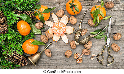 Christmas decoration with tangerine fruits and walnuts on wooden background