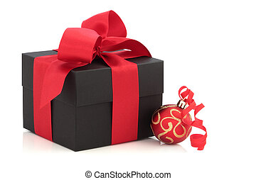 Christmas gift box tied with a satin bow, with red and gold sparkling bauble and ribbon, isolated over white background.