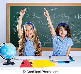 clever students in classroom raising hand with blackboard background