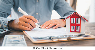 Close up hand signing signature loan document to home ownership. Mortgage and real estate property investment, home insurance ,security
