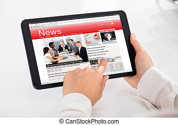 Person Reading News On Digital Tablet