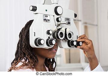 Optometrist's Hand Adjusting Phoropter