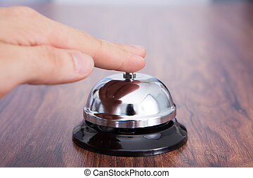 Close-up Of Hand Ringing Service Bell Kept On Wooden Table