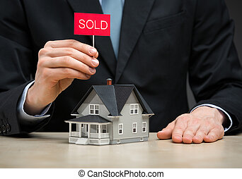 Close up of little house and hand keeping sold tablet