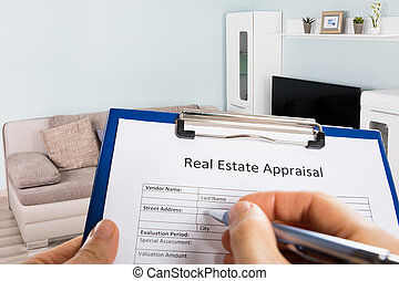 Person Hand Filling Real Estate Appraisal Document