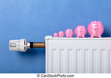 Pink Piggy Banks Kept In A Row On Radiator
