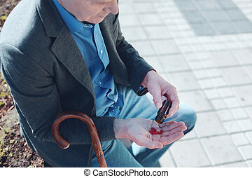 Close up of senior man taking pills outdoors