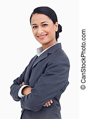 Close up of smiling saleswoman with arms crossed against a white background