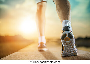 A person running outdoors on a sunny day. Only the feet are visible. The person is wearing black running shoes. Exercise, fitness and healthy lifestyle.