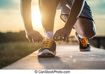 Man tying jogging shoes. A person running outdoors on a sunny day. The person is wearing black running shoes. Focus on a side view of two human hands reaching down to a athletic shoe.