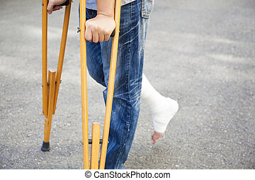 closeup of leg on bandage with crutches