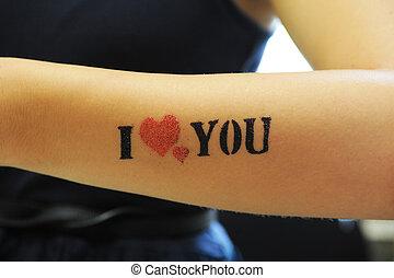 """closeup of tatoo """"I love you"""" at woman hand"""