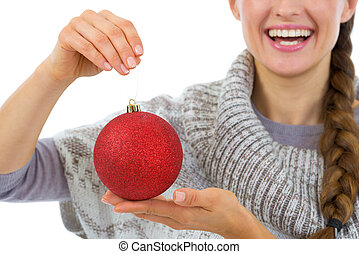 Closeup on Christmas ball in hand of smiling woman