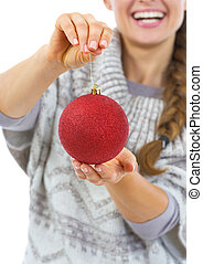 Closeup on christmas ball in hand of young woman in sweater