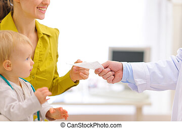 Closeup on pediatric doctors hand giving prescription to mother with baby