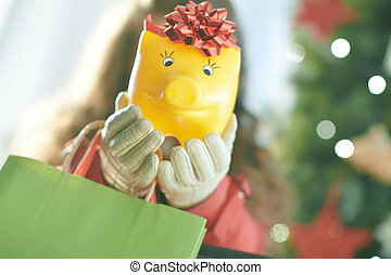 Closeup on yellow piggy bank in hand of woman shopper