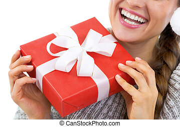 Closeup on young woman in sweater holding christmas present box