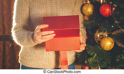 Closeup toned image of woman in sweater opens box with Christmas present