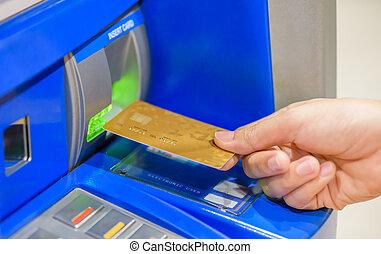 Closeup woman hand inserting debit card into an ATM machine.