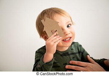Clumsy toddler boy trying to look through paper house window