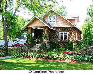 Cobblestone House with green grass and beautiful garden / landscaping