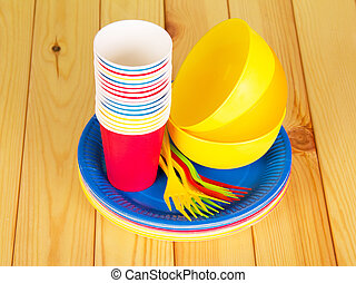 Colorful disposable tableware on a wooden table