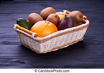 Colorful organic fruits in wicker basket.
