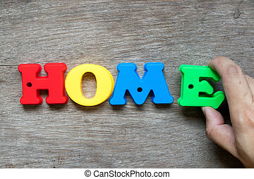 Colorful plastic alphabet in word home with hand hold E to fulfill on wood background (Concept of dream home, happy family, mortgage loan, property ownership)