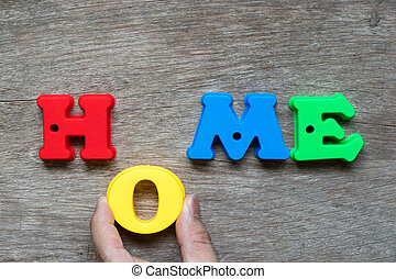 Colorful plastic alphabet in word home with hand hold O to fulfill on wood background (Concept of dream home, happy family, mortgage loan, property ownership)