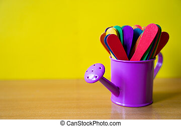colourful wooden stick in a violet watering pot on wooden table with yellow backgound. education, creative and art concept