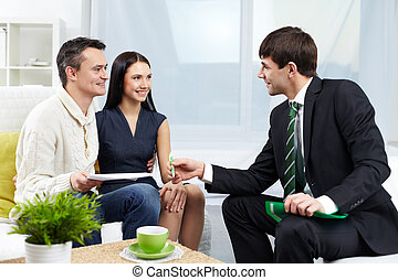 Portrait of modern couple looking at manager while discussing agreement