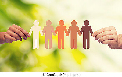 community, unity, people and support concept - couple hands holding paper chain multiracial people over green background