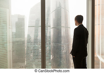 Company official looking through window in office