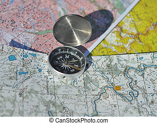 The compass on the map. Open the compass lies on topographic maps and casts a shadow over them.