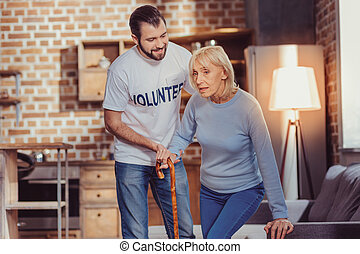 Concentrated ill woman holding a cane and trying to stand up.