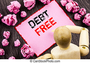 Conceptual hand text showing Debt Free. Concept meaning Credit Money Financial Sign Freedom From Loan Mortage written on Sticky Note Holding By Sculpture on the wooden background.