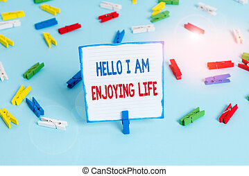 Conceptual hand writing showing Hello I Am Enjoying Life. Business photo text Happy relaxed lifestyle Enjoy simple things Colored clothespin papers empty reminder blue floor officepin.